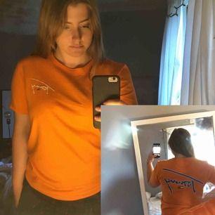 Orange t-shirt med blått Tommy tryck på ryggen och ärmen och bröstet. Nypriset var 650kr på asos. Knappt använd och i jätte bra skick. Frakten står köparen för