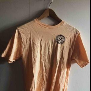Info: Vans t-shirt, har samma logga både fram och bak. Är en herrtröja men kan användas som unisex. Köpdatum: Köptes förra sommaren och är inte använd så mycket. Köppris: Ca 400 kr.  Färg: Peach/orange  FRAKT INGÅR I PRISET