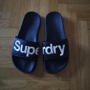 Badtofflor/pool slides från Superdry med stor logo som kan användas till vardags på sommaren också. Stl M vilket motsvarar stl 42-43. Rekommenderar vita höga tubsockor i sandaler för den vågade! Frakt 63 kr.
