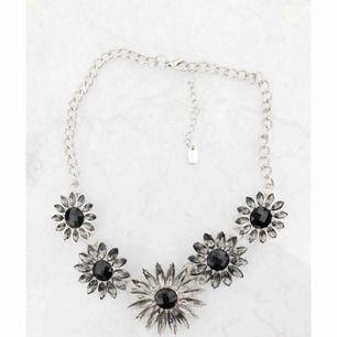 Silvrigt halsband med blommor.