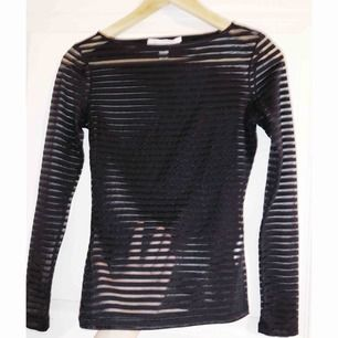 Tight genomskinlig tröja med svarta ränder. Från Nelly trend.