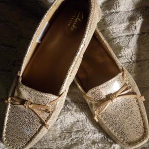 Oanvända loafers från Clarks i guld o brunt kommer med original kartong. Nypris 1.099kr  Frakt betalar köparen
