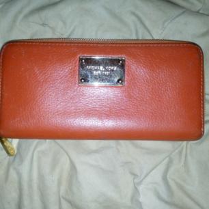 Orange plånbok i skinn fr Michael Kors, i mkt gott skick, inga fläckar eller andra skador förutom att märket är lite repigt, naturligtvis äkta!  Köparen betalar frakt 55kr