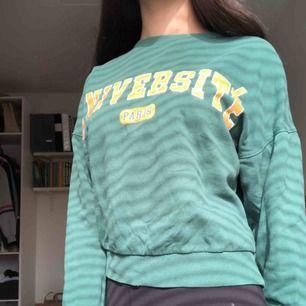 Grön sweatshirt med gult tryck från ginatricot. Använd ett fåtal ggr men typ i nyskick. Köparen står för frakt.