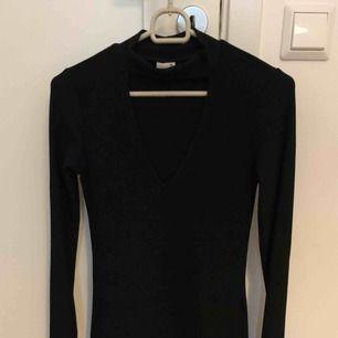 En svart och väldigt snygg v-ringad klänning från Gina Tricot