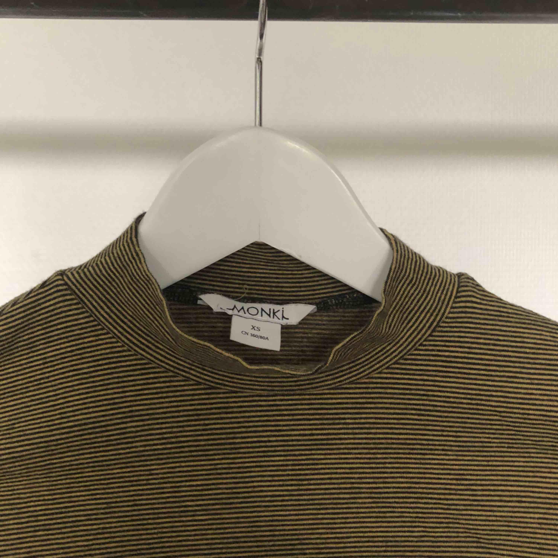 En fin polo t-shirt från Monki! Svart och gul randig, med tajt passform. För mer bilder är det bara att skriva, frakt tillkommer! 💛🖤. Toppar.