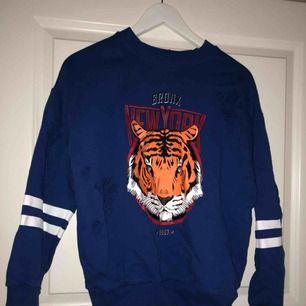 Cool blå collagetröja/sweatshirt med tryck på framsidan och slitningar, bra skick