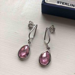 *Nedsatt från 175kr till 125kr!  Äkta silverörhängen med rosa sten från brittiska märket Paul Kennedy. Aldrig använda! Legat i asken hela tiden. Fått dem i present men de är tyvärr inte min stil.  Tar swish! Kan mötas upp i Stockholm!