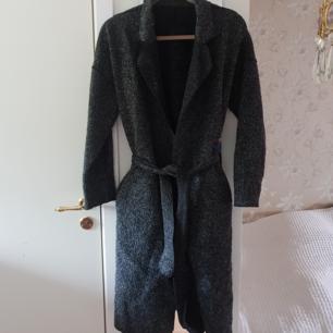 Längre och tunnare kappa i melerad polyester och ull. Använt skick.