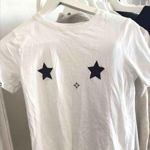 Vit T-shirt med stjärnor över brösten.