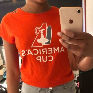 En T-shirt, lite roligare än döm vanliga från sail racing. Orange/rödfärg. Passar Xs