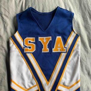 Vintage cheerleadertröja, hittat på second hand. Använd ett fåtal gånger. Mycket stretchigt material, är lite som en lång magtröja.