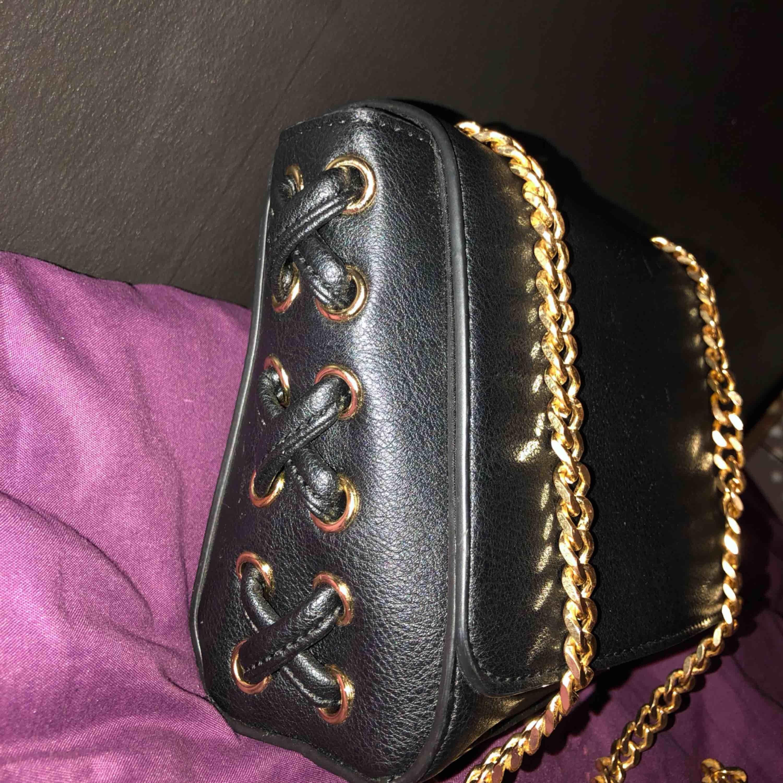 Ny fin svart axel väska med gulddetalj och kedja axelband väldigt fin.  Finns i Västerås att hämta eller postas och köparen står för frakten.. Väskor.