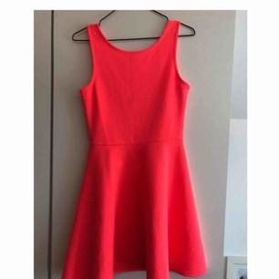 Neonfärgad klänning som går ner till mitten av låren. Bra skick. Går ner som en urringning i ryggen (visas på bild 2). Jag har 38 i vanliga fall men den är lite för liten så skulle säga att det är mer en 36 i storleken.