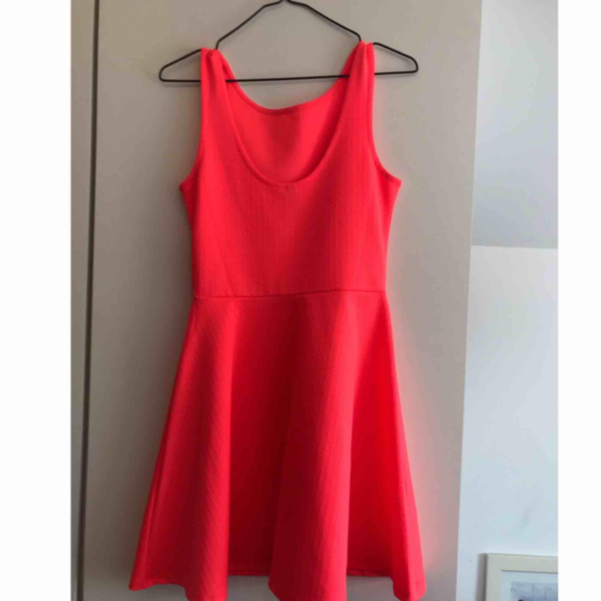 Neonfärgad klänning som går ner till mitten av låren. Bra skick. Går ner som en urringning i ryggen (visas på bild 2). Jag har 38 i vanliga fall men den är lite för liten så skulle säga att det är mer en 36 i storleken.  . Klänningar.