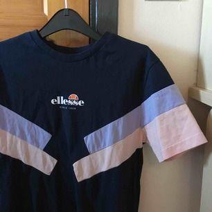 💙 Säljer en marinblå Elesse t-shirt med rosa och lila detaljer. Helt nytt skick, aldrig använd. Köparen står för frakt
