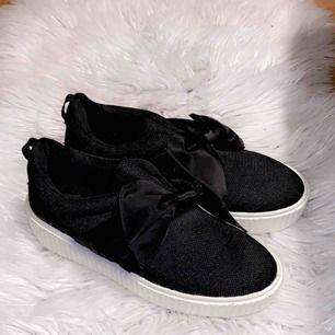 Svarta sneakers med rosett på.