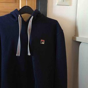 💙 Säljer en marinblå FILA-hoodie i storlek M. Hoodien är ganska liten i storleken och kan passa S. Använd fåtal gånger och i helt nytt skick. Köparen står för frakt :)