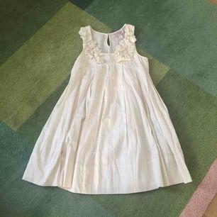 Vacker créme-färgad klänning från H&M Garden Collection. Fantastiskt tyg med fin glans och fickor.
