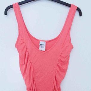 Korallfärgade klänning i Stl M från ginatricot. Stretchig. Material 92% viskos, 8% elastan