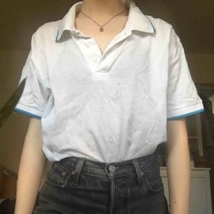 Vit piké-liknande tröja med blå kant på kragen. En aning genomskinlig och tillräckligt luftig för att kunna ha nu på sommaren. Storlek L men passar perfekt som en oversized tröja på mig (XS/S) Säljer då den aldrig kommer till användning.