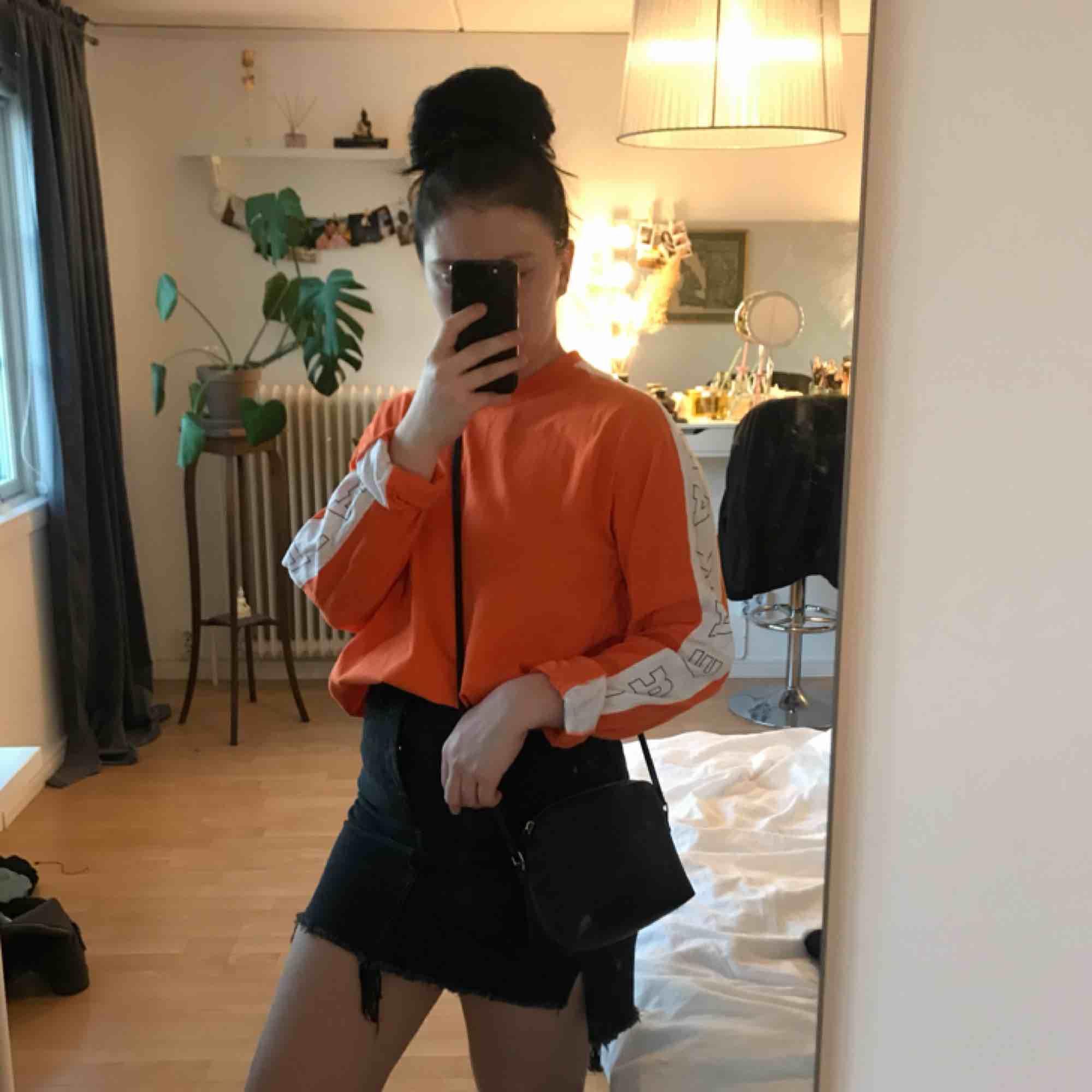 Svinsnygg orange tröja med text på ärmarna. Storleken är L från killavdelningen men passar alla mellan XS och L. Gillar när den är lite stor och jag är en S🧡🧡. T-shirts.
