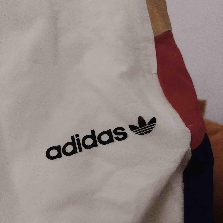 """Info: LIMITED EDITION adidas wind pants med röd-blå-guldiga detaljer på benen. Väldigt snygga och bekväma! Färg: Vita med gul,röd,blåa ränder på benen. Finns även en """"adidas"""" text med logga på vänster ben. Jeans & Byxor."""