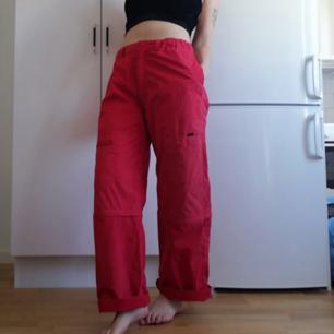 Röda vintage cargobyxor i stl S. Ganska rymliga och suoersköna! Fullt av fickor, och avtagbara ben som går att göra om till shorts. Midjemått 78-90 cm beroende på om de är utstretchade och innerbenslängd 74 cm, har dock vikt upp dem lite på bilderna. Jag på bilden har XS. Frakt 59 kr.