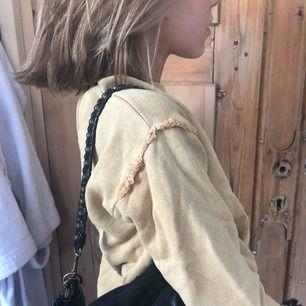 En brun gul tröja med rufflade detaljer runt axeln. Bra kvalite och blir inte nopprig. Sitter fint på!