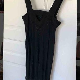 Jättefin svart knälång sidenklänning från Tiger of Sweden med dekorativa påsydda pärlor. Storlek medium. Använd en gång.