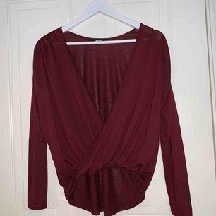 Vinröd omlott tröja med djup ringning. Köpt från bikbok använd 2 gånger. Frakt tillkommer.