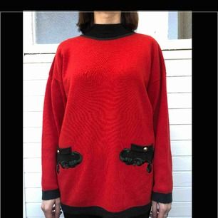 Röd vintage tröja med fickor från Moda styl. 70% ull och 30% akryl. Den är i bra begagnat skick och har inga hål eller fläckar. Den har svarta kanter. Den är gjord i Italien.  Personen på bilden är 158 cm.