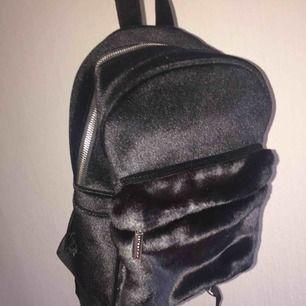 Väska eller ryggsäck i svart sammetliknande material! Använd någon fåtal gång men helt som ny. Köpt från ASOS. Väldigt fin men har inte kommit till användning, möts upp i Stockholm! Skriv om ni har övriga frågor :)