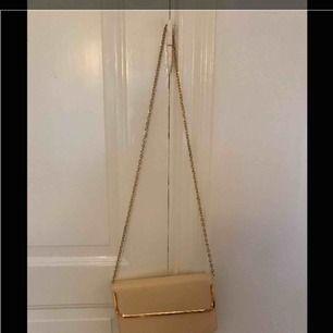 Biege kuvertväska med guldig kedja från Forever 21. Lite missfärgad på baksidan.