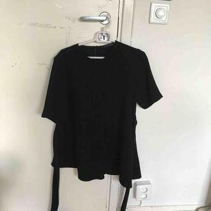Fin svart t-shirt blus från zara med knytning runt midjan. Den ena sidan är även lite längre än den andra men det är svårt att se på bilden. Köparen står för frakten