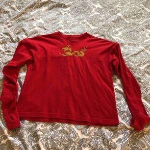 Röd långärmad t-shirt med gul/guldig drake på bröstet. Använd fåtal gånger. Köpt på carlings. Köparen står för frakten eller möts upp i Linköping.