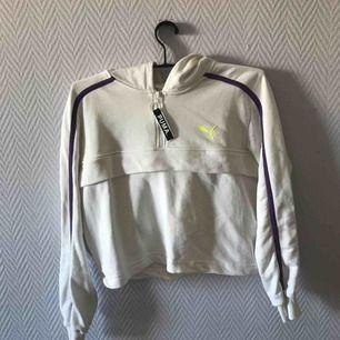 Cropped vit hoodie från puma, med detaljer halv dragkedja å ficka med dragkedja.  Använd 2 gånger så jätte bra skick Kan mötas upp i Malmö annars står köparen för frakten
