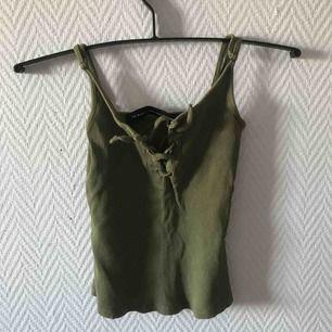 Grönt linne med snörning över brösten. Säljer pga använder ej Kan mötas upp i Malmö annars står köparen för frakten