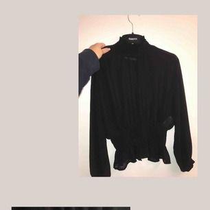 En genomskinlig fest tröja/blus, med en krage och volanger, storlek Xs  Om det ska skickas, frakt tillkommer 59kr totalt för tröjan då.