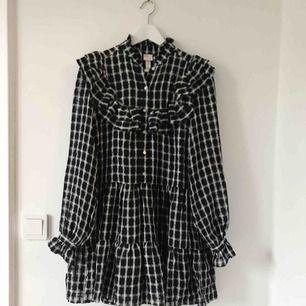 Superfin och populär svart- och vitrutig volangklänning från H&M trend, stl XS/34. Påminner om en GANNI-klänning. Använd en gång så i nyskick!