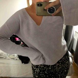 Säljer en ribbstickad ljuslila långärmad tröja med utsvängda ärmar. Tröjan är V-ringad och inte så lång. Den är i gott skick och inte använd mycket alls