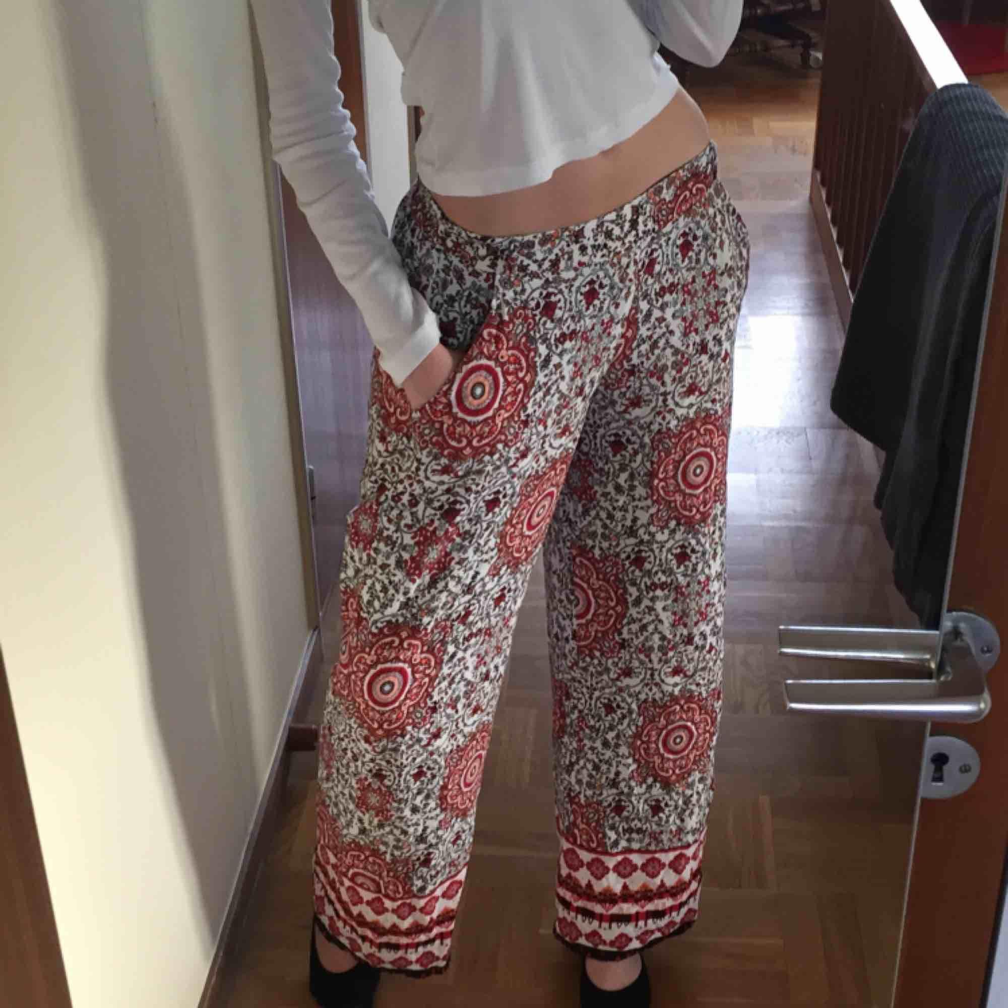 """Lösa """"flowy"""" byxor i ett detaljerat rött mönster. I storlek 38 eller L men dom är mindre i midjan. Rätt långa då jag är 178cm och de är perfekt i längden på mig! Möts upp i Stockholm, skriv om ni har frågor eller vill ha fler bilder! :). Jeans & Byxor."""