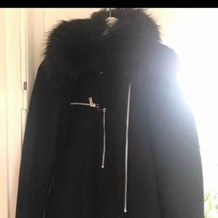 Klassisk svart kappa från ZARA strl 36. Avtagbar fuskpäls som ser väldigt fin ut för att vara fejk. Fejk skindetaljer samt dubbla dragkedjor   Inkl frakt
