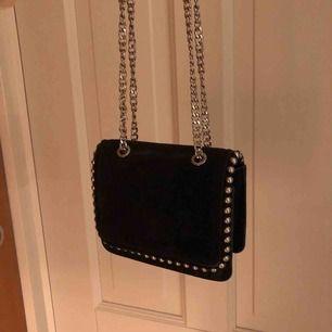 """Mocka väska i mörkblå/svart. Den är liten med en lång kedja som man antingen kan ha över kroppen eller om man """"tar upp"""" kedjorna så det blir mer av en axelväska. Passar fint till vardag och fest. Bra kvalite, köpt för 600kr från början"""