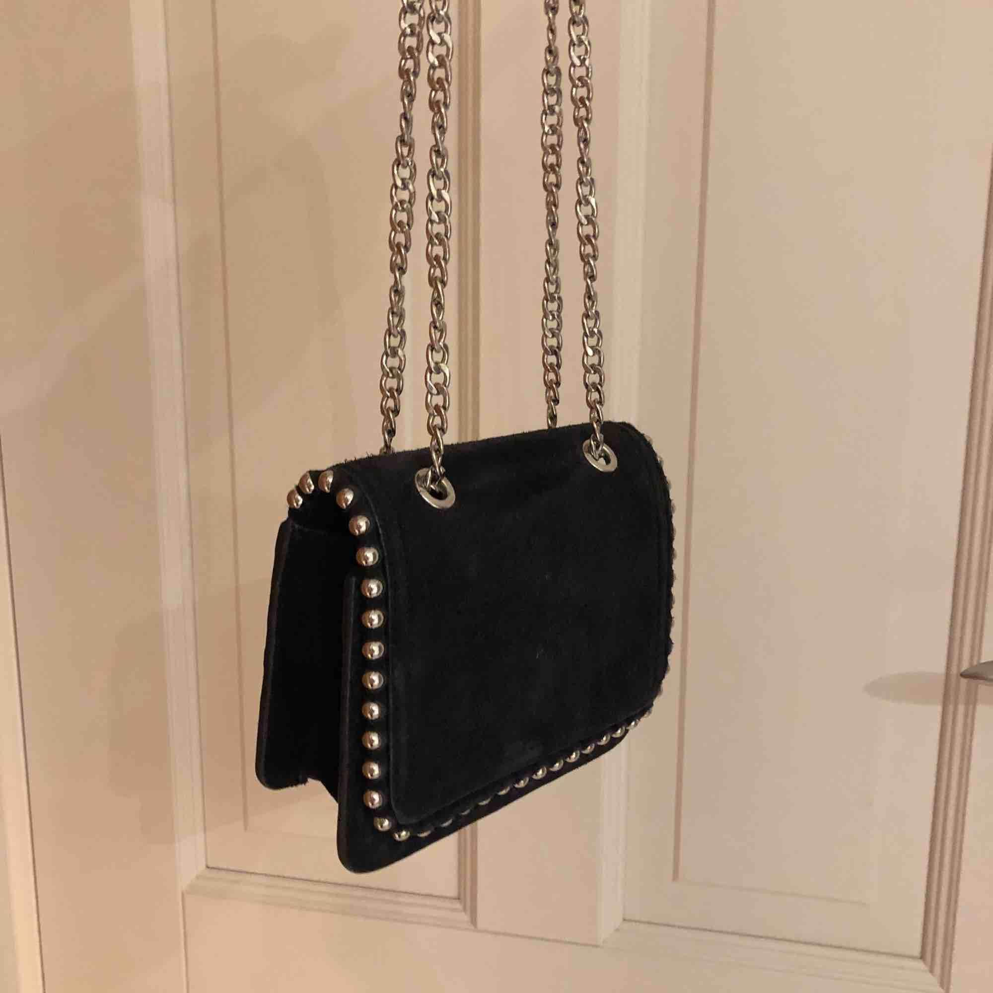 """Mocka väska i mörkblå/svart. Den är liten med en lång kedja som man antingen kan ha över kroppen eller om man """"tar upp"""" kedjorna så det blir mer av en axelväska. Passar fint till vardag och fest. Bra kvalite, köpt för 600kr från början . Väskor."""