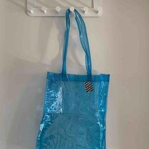 En blå genomskinlig väska som är köpt på humana.                  Storlek: 37 cm hög och 30 cm bred. Säljer för 80kr ink frakt❤️