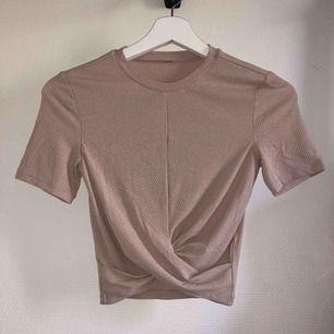 """Gammelrosa/ljusrosa topp med """"knytdetalj"""" framtill. Från H&M. Har aldrig använt den, men klippte bort lapparna då jag trodde jag skulle göra det"""