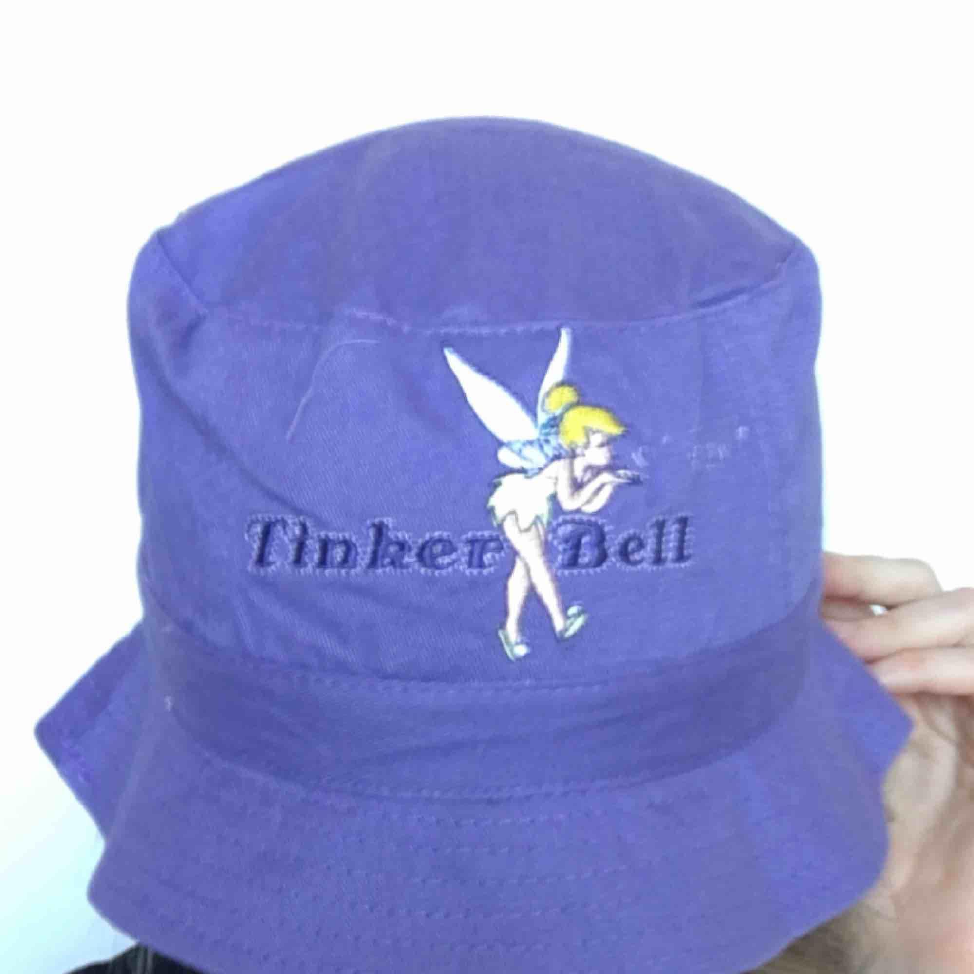 🍒BuCKET PUPPET🍒 QT buckethatt i lila med Tinkerbell broderi framtill. så fin att styla till bby rosa för äkta y2k stil. Det är en barnstorlek så passar mindre storlekar. Frakt tillkommer. Puss o K🍒. Accessoarer.