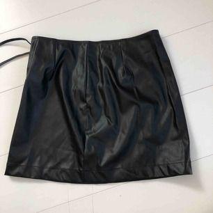 Tight svart fake läder kjol med knytning på sidan. Slutar som en vanlig kjol (går att sitta utan att den åker upp). Den är i nytt skick aldrig använd