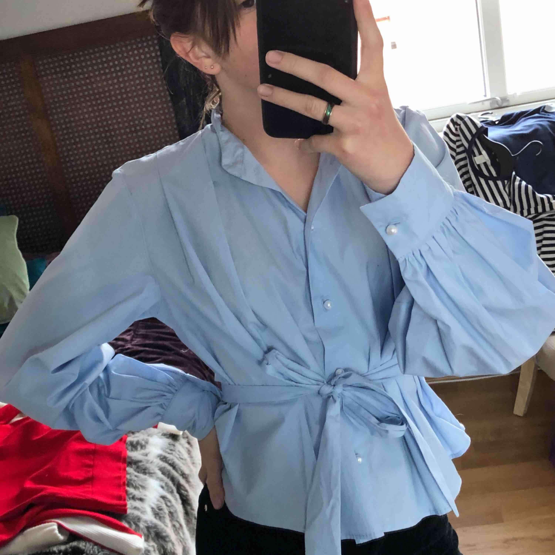 Jättefin ljusblå skjorta från hm, helt oanvänd i jättebra skick. Den är lite kortare i modellen. Frakt tillkommer :) . Skjortor.